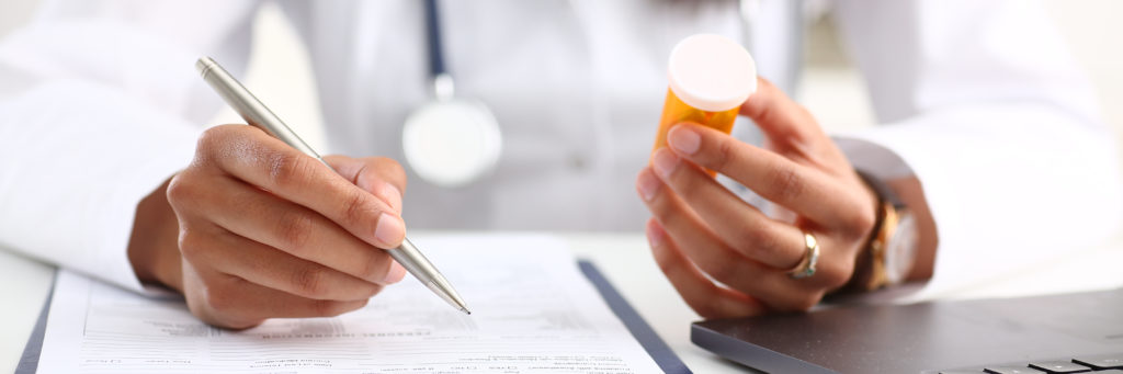 Doctor holding prescription pill at patient appointment